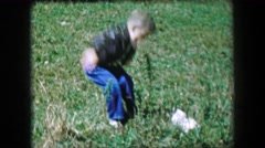 1957: Boy surprised by lost stray cat jumping in long grass petting kitten. Stock Footage