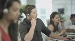 4K Customer service ops taking calls in busy call center with manager overseeing Arkistovideo