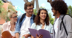 Friends interacting while reading books Stock Footage
