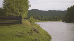Wooden fence is on one side of large river, trees and mountain on other Stock Footage