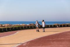 Girls Skating Beachfront Ocean Promenade - stock photo