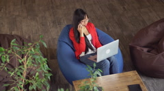 Asian woman working in loft sitting on bean bag chairs Stock Footage