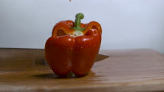 A red bell pepper being chopped in half on a cutting board in slow motion. Stock Footage