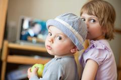 Little boy and girl turned around looking through their shoulders Stock Photos