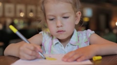 Little girl draws in the cafe waiting for the order. child in restaurant Stock Footage