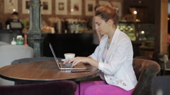 Young beautiful business lady working on laptop, sitting in cozy cafe Stock Footage