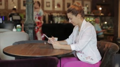 young beautiful business lady working on tablet computer, sitting in a cozy cafe - stock footage