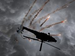 Silhouette of an attack helicopter firing flares - stock photo