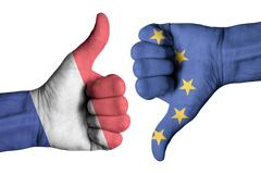 France and Europe flag on human male thumb up and down hands - stock photo