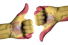 Spain flag on human male thumb up and down hands Stock Photos