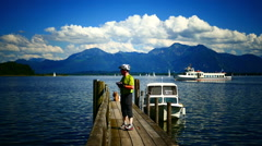 Tourist taking picture on wooden bridge in Prien Chiemsee lake Germany Stock Footage