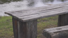 On riverside on green meadow stand old used wooden table and bench Stock Footage