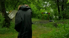 Man Walking by Tourist Base People in a Tents Camp in the Pouring Rain Lush Stock Footage