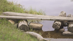 Homemade wooden bridge from logs and stones built in calm river Stock Footage