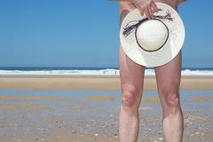 Naked man posing with hat nude, on beach - stock photo