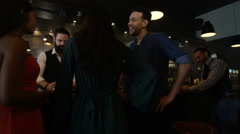 4K Young diverse group socializing & bartender serving drinks in trendy city bar Stock Footage