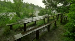 Old Wooden Tables and Benches in the Pouring Rain Tourist Base Lush Green Trees Stock Footage