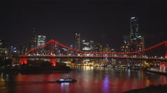 Night shot of a ferry and brisbane's story bridge Stock Footage