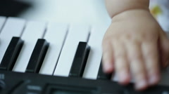 Baby hand on an electronic digital music keyboard Stock Footage
