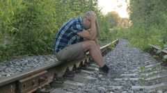 The man is sitting on the rails holding his head. Stress, depression, lonelin - stock footage