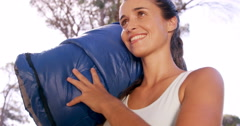 Woman holding a sleeping bag outside the tent Stock Footage