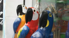 Close up of three large carved wooden macaws in rio Stock Footage