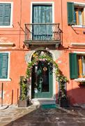 Pretty rose arbor over a door on Burano, Venice - stock photo