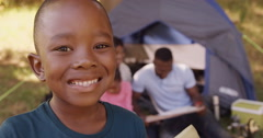 Child smiling at camera in front of a tent Stock Footage