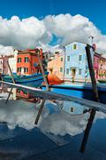 Colorful houses of Burano reflected in a puddle Stock Photos