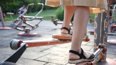 Fitness training ground in the park - woman legs twist the bicycle pedals Stock Footage