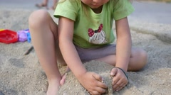Little child girl funny playing in sandbox with sand on a big park playground Stock Footage
