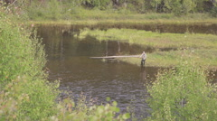 On swampy riverbank fisherman threw long bait and waits for fish Stock Footage