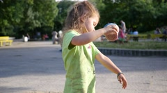 Little child girl funny playing in sandbox with sand on a big park playground - stock footage