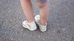 Little child girl legs in sandals walking over asphalt footpath in the park Stock Footage