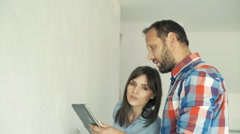 Young couple talking and using tablet during painting their new home Stock Footage