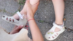 Mom wears sandals on foot of her little child girl daughter during walking Stock Footage