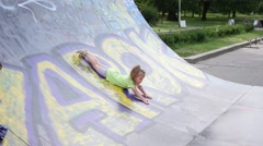 Little kid girl have fun playing sliding down on a ramp for riding skates Stock Footage
