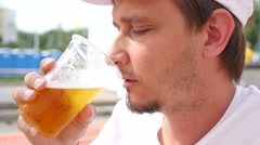 Man drinking beer outdoors - football fan during watching a match on big screen Stock Footage