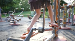 Fitness training ground in the park - kid girl legs twist the bicycle pedals Stock Footage