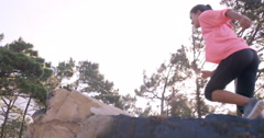 Sportswoman raising her hands after climbing rock Stock Footage