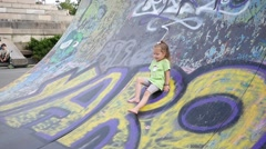 The ramp for skaters and rollerbladers - little girl slides down on her butty Stock Footage