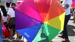 Rainbow umbrella at gay pride parade. Stock Footage