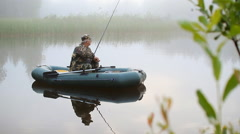 Fisherman on the boat throws the bait. Early morning fog on the lake Stock Footage