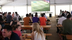 Tent bar for football fans - watching the match with a beer on the big screen Stock Footage