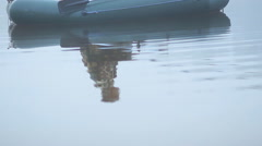 A fisherman in a boat with a fishing rod waiting for the fish. Early morning fog Stock Footage