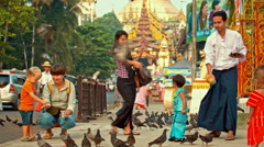 Feeding pigeons at the entry to the Shwedagon Pagoda Stock Footage