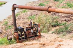 Old and rusty pump with big steel pipe pumping water from lake - stock photo