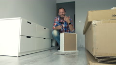Young man hurt himself during assembling furniture in his new home, 4K - stock footage