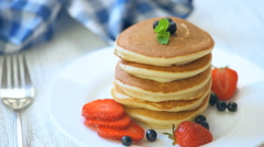 Pancakes with berries and maple syrup - stock footage