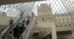 People riding escalators underground the Louvre Pyramid Stock Footage
